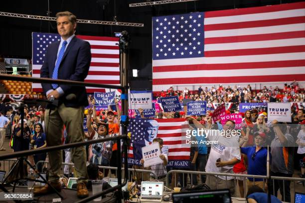 CNN reporter Jim Acosta works as supporters of US President Donald Trump shout toward members of the press before the start of a rally at the...