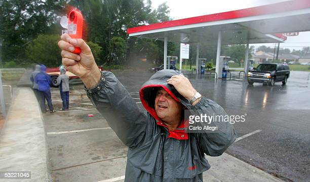 CNN reporter John Zarrella takes a reading of the wind as he prepares to give a live report before hurricane Dennis makes landfall July 10 2005 in...