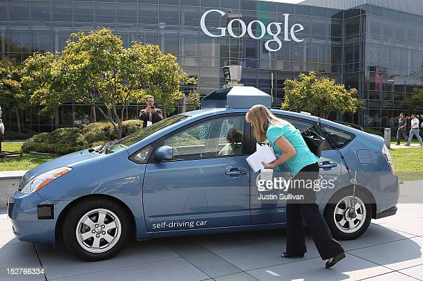 A reporter looks at a Google selfdriving car at the Google headquarters on September 25 2012 in Mountain View California California Gov Jerry Brown...