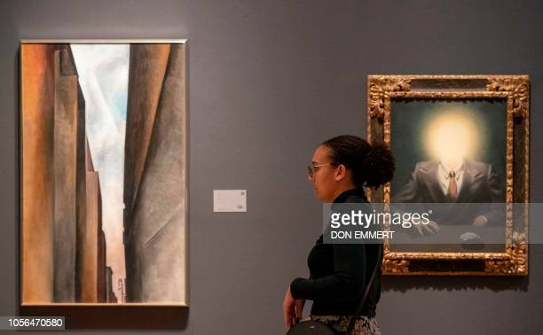 A reporter looks at Georgia O'Keeffe's A Street and René Magritte's Le Principe Du Plaisir on November 2 2018 at Sotheby's Auction house in New York...