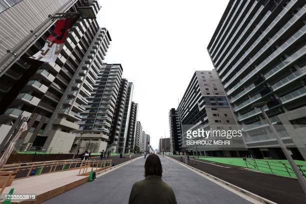 Reporter looks at the buildings which will host the athletes during the 2020 Tokyo Olympic Games, during a media tour of the Olympic Village in Tokyo...