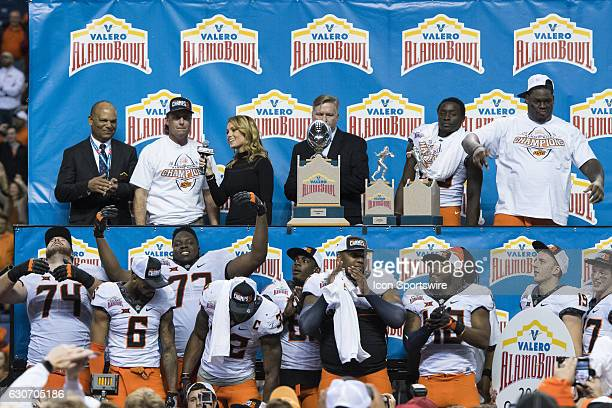 ESPN reporter Molly McGrath speaks with Oklahoma State Cowboys head coach Mike Gundy during the Valero Alamo Bowl between the Colorado Buffaloes and...