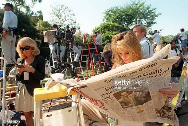 TV reporter Pat Lalama reads a newspaper headlining the not guilty verdicts of OJ Simpson as she and hundreds of members of the press staked out the...