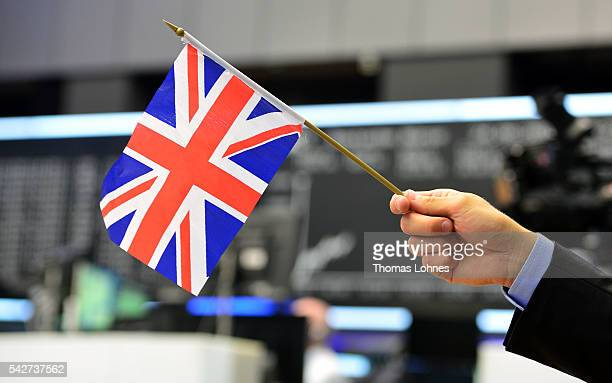TV reporter pose with a Great Britain flag at the Frankfurt Stock exchange the day after a majority of the British population voted for leaving the...