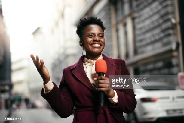 tv reporter presenting the news outdoors. - journalist stock pictures, royalty-free photos & images