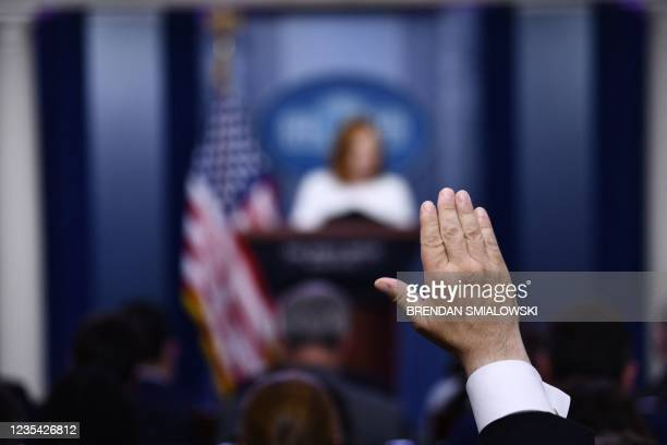 Reporter raises his hand as White House Press Secretary Jen Psaki holds a press briefing in the Brady Briefing Room of the White House in Washington,...