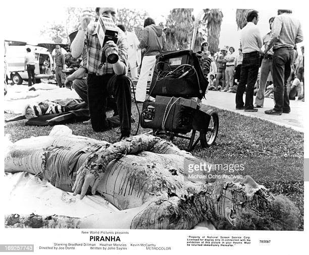 Reporter records the remains of a corpse in a scene from the film 'Piranha', 1978.