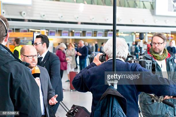TV reporter reporting from a strike at the Frankfurt Airport