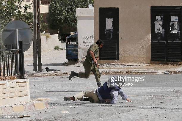 Reporter Sammy Ketz, hits the ground as a Syrian soldier runs past during sniper fire in the ancient Christian Syrian town of Maalula, on September...
