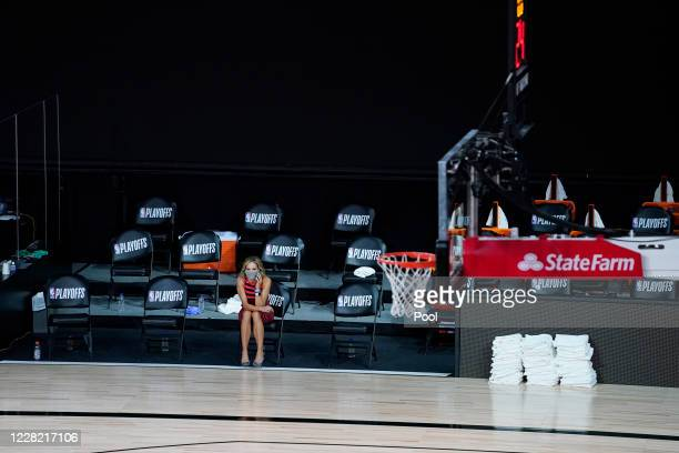 Reporter sits beside an empty court after a postponed NBA basketball first round playoff game between the Milwaukee Bucks and the Orlando Magic at...