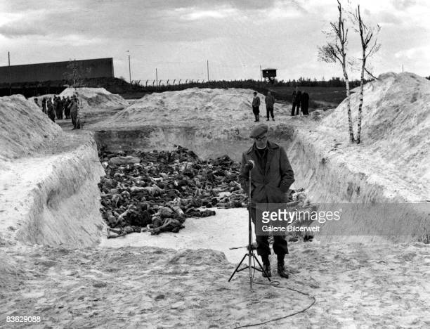 Reporter stands in front of a mass grave at Bergen-Belsen concentration camp, after its liberation by the British army, April 1945. 60,000 civilian...