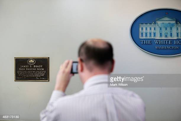 Reporter takes a photograph of a plaque honoring former White House Press Secretary James S. Brady in the James Brady Press Briefing Room at the...