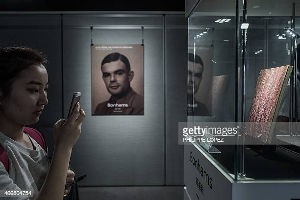 A reporter takes a picture of a rare manuscript belonging to British mathematician and code breaker Alan Turing on display in Hong Kong on March 19...