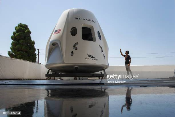 Reporter takes a smart phone photo of a mock up of the Crew Dragon spacecraft during a media tour of SpaceX headquarters and rocket factory on August...