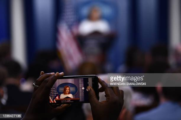 Reporter takes a video as White House Press Secretary Jen Psaki holds a press briefing in the Brady Briefing Room of the White House in Washington,...