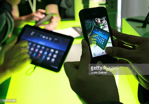 A reporter uses a cell phone to take a photograph of Google Android 30 Honeycomb OS being used on a Motorola Xoon tablet during a press event at...