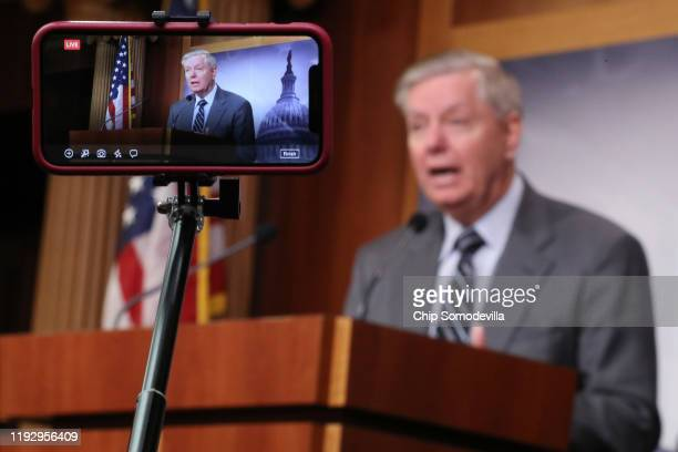 Reporter uses her iPhone to record Senate Judiciary Committee Chairman Lindsey Graham as he holds a news conference following the release of the...