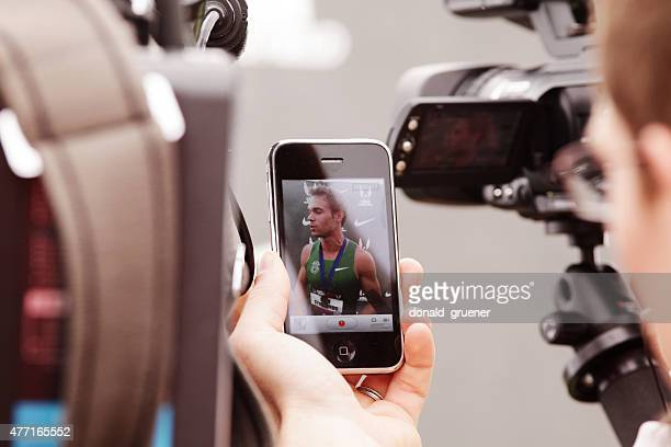 Reporter using smartphone to record Nick Symmonds post-win press conference