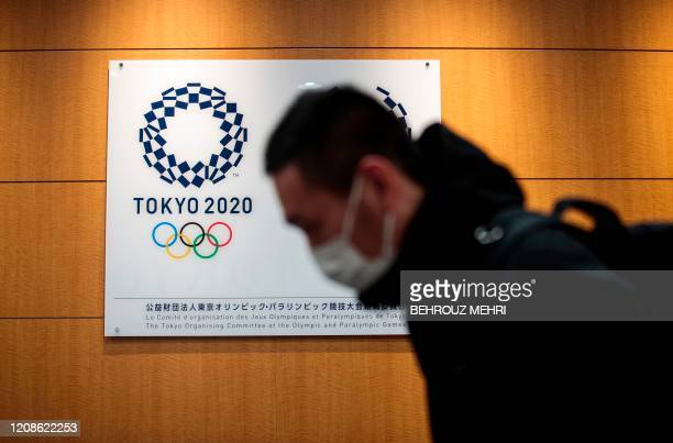 A reporter walks past a logo of the Tokyo 2020 Olympic Games after a press conference at the Tokyo 2020 headquarters in Tokyo on March 30 2020 The...