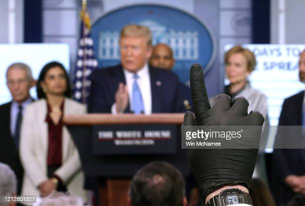 A reporter wearing a latex glove raises his hand to ask US President Donald Trump a question during Coronavirus briefing at the White House on March...