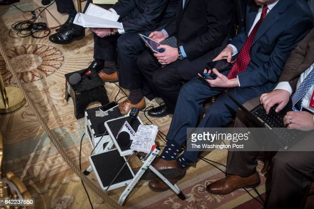 Reporters and members of the media takes notes and listen as President Donald Trump speaks during a press conference in the East Room of the White...
