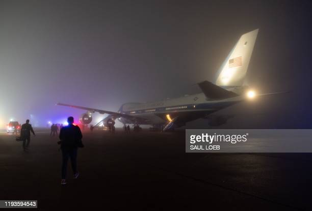 Reporters and staff board Air Force One in heavy fog prior to departing from Louis Armstrong New Orleans International Airport in Kenner Louisiana...
