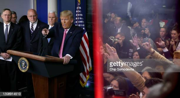 Reporters are reflected in an 'EXIT' sign as U.S. President Donald Trump calls on reporters during a news conference with members of his coronavirus...