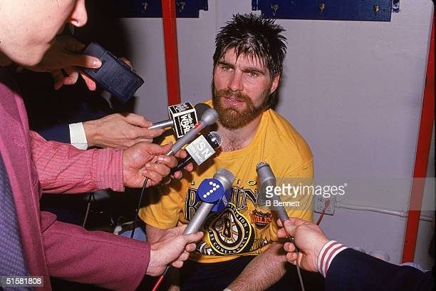 Reporters armed with microphones interview Canadian professional ice hockey player defenseman Ray Bourque of the Boston Bruins after the Bruins...