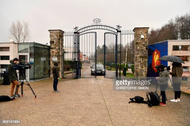 Reporters broadcast from the front entrance of the headquarters of the French Rugby Federation while a car drives through the gates on January 23...