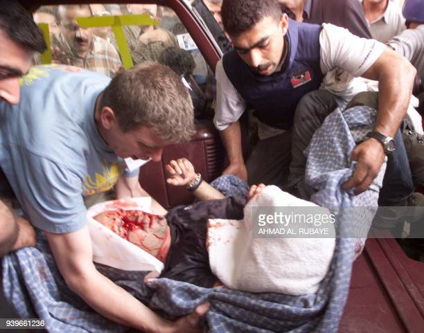 Reporters carry fatally wounded Reuters cameraman Taras Protsyuk, a 35-year-old Ukranian national, out of the Palestine hotel 08 April 2003. Four...