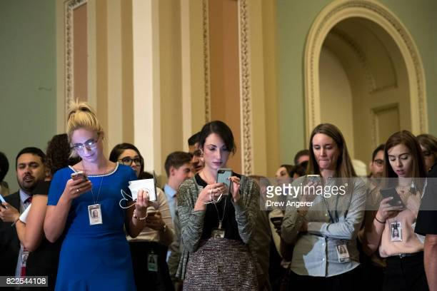 Reporters check their phones as Senators hold a procedural vote on the GOP heath care plan on Capitol Hill July 25 2017 in Washington DC The Senate...