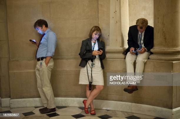 Reporters check their smartphones while waiting outside US House Speaker John Boehner's office at the US Capitol in Washington on September 30 2013...