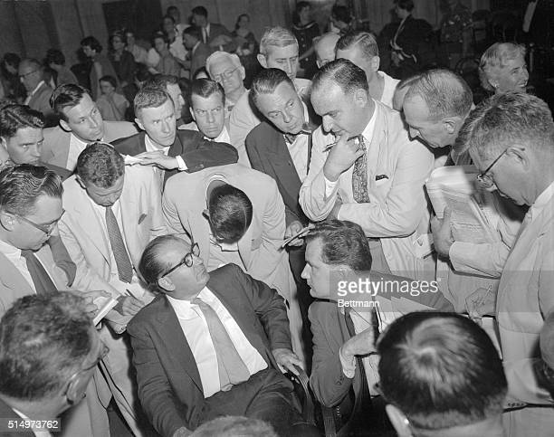 Reporters completely surrounding Sen. Joseph McCarthy and his attorney Edward Williams listen intently to a question being asked by one of their...