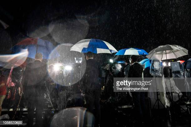 Reporters do live television hits in the rain on a riser before the polls close and Tallahassee Mayor and Democratic nominee for Governor of Florida...