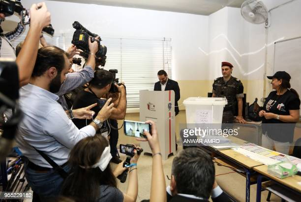 Reporters gather around Lebanese Prime Minister Saad Hariri as he casts his vote at a polling station in the capital Beirut on May 6 2018 as the...