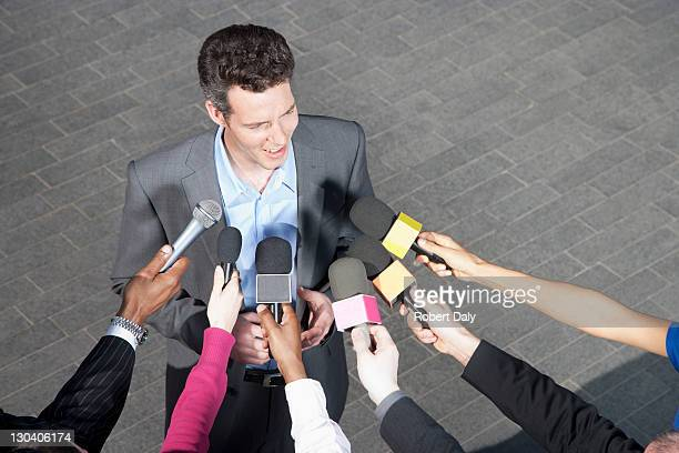 reporters holding microphones for politician - politician stock pictures, royalty-free photos & images