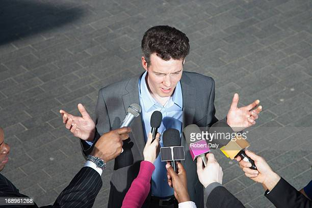 Reporters holding microphones for politician