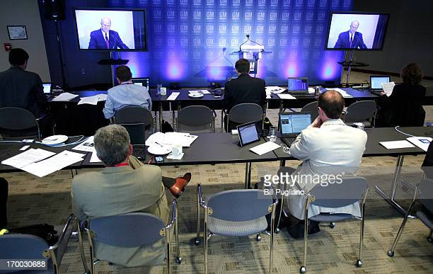 Reporters in the press room watch the video monitors and listen to General Motors Chairman and CEO Dan Akerson speak at the GM Annual Shareholders...