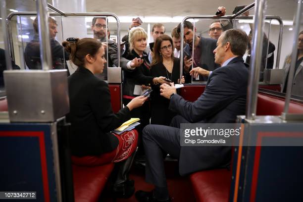 Reporters lean into a subway car while asking Sen John Thune questions following the weekly Senate Republican policy luncheon in the US Capitol...