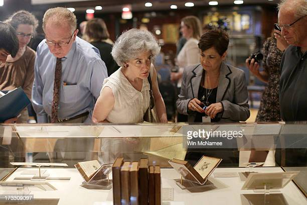 Reporters lean over a glass case to view books and papers that belonged to George Washington following a press conference at the National Press Club...
