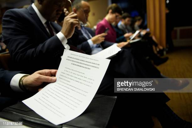 Reporters look at an opening statement from US Attorney General William Barr before a press conference about the release of the Mueller Report at the...