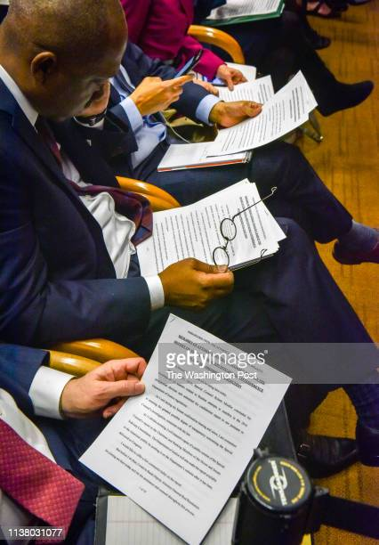 Reporters look at printed remarks handed to them just before Attorney General William Barr holds a press conference hours before releasing a lightly...