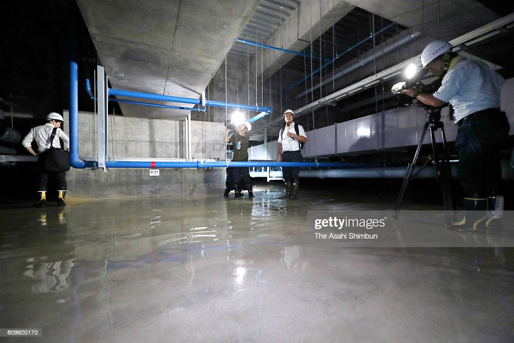 Reporters On Check The Water Level Covering The Concrete Floor Of