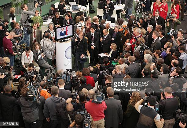 Reporters photographers and television crews gather round a TV monitor to listen as US President Barack Obama address delegates at the final day of...
