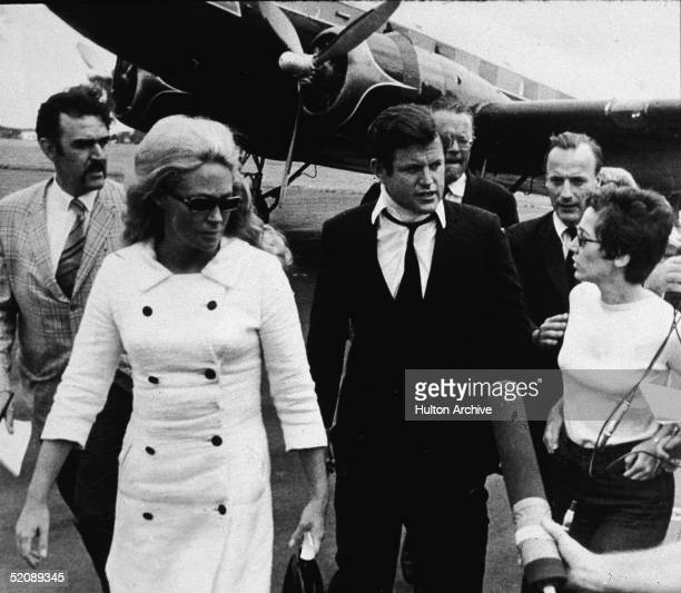 Reporters question American Senator Edward Kennedy and his wife Joan Kennedy as they walk across the tarmac after returning from the funeral of Mary...