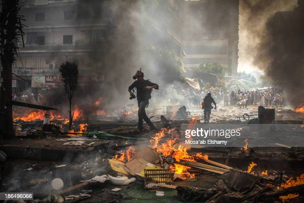 Reporters run for cover during the violent clearing of Rabaa Adaweya camp by security forces, which left at least 800 killed.