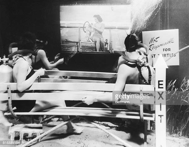 Reporters sit on benches at the premiere of Underwater as the star of the film Jane Russell appears on the plastic screen Miss Russell was in the...