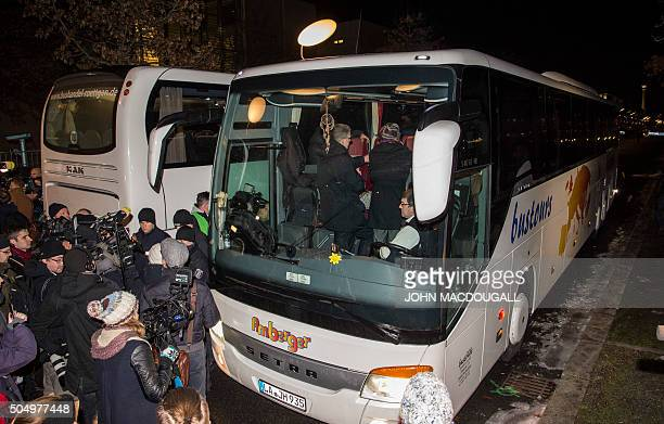Reporters surround a bus carrying refugees parked in front of the chancellery in Berlin on January 14 after it arrived from the Bavarian city of...