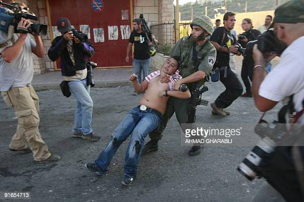 Reporters surround an Israeli border policeman as he detains a Palestinian youth who was throwing stones during clashes on October 05 2009 in the...