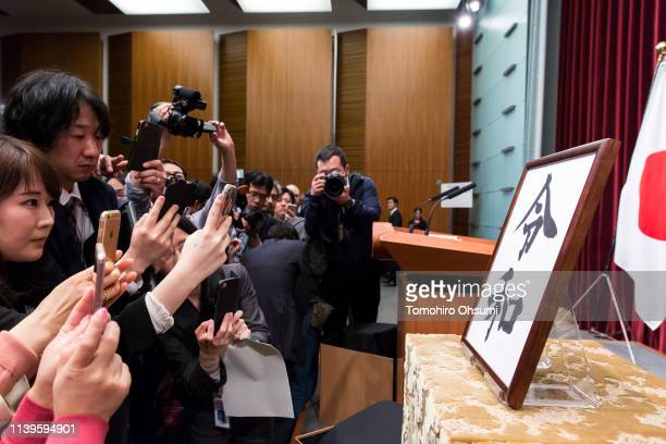 Reporters take photographs of a calligraphy with new era name 'Reiwa' before a press conference by Japan's Prime Minister Shinzo Abe on April 1 2019...